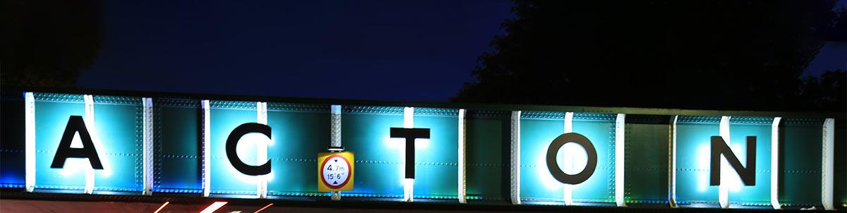 Acton bridge sign at night